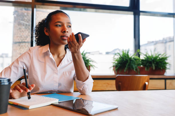 Young business woman conducts negotiate from cafe, using her smartphone stock photo