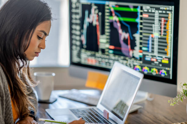 Young business woman day trading from her dining room table stock photo
