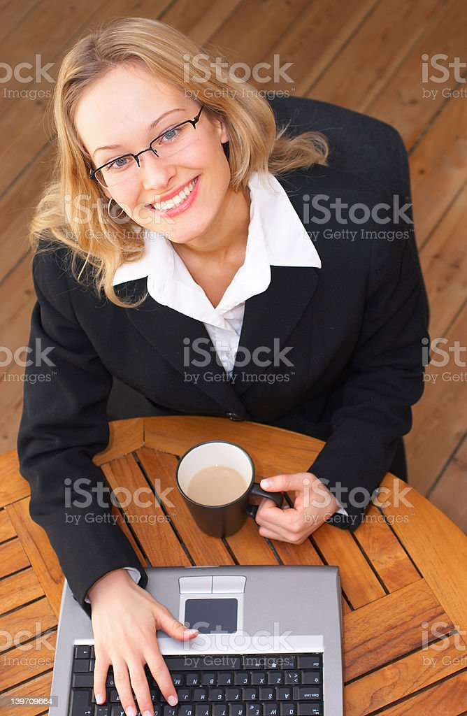 Young Business Woman drinking coffee and doing work (smiling) royalty-free stock photo