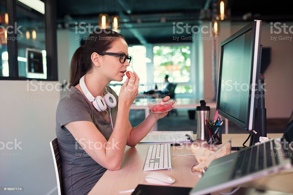 Young business woman eating a tomatoes in front of pc stock photo