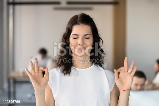 istock Young business woman employee meditating in office with eyes closed 1128967681