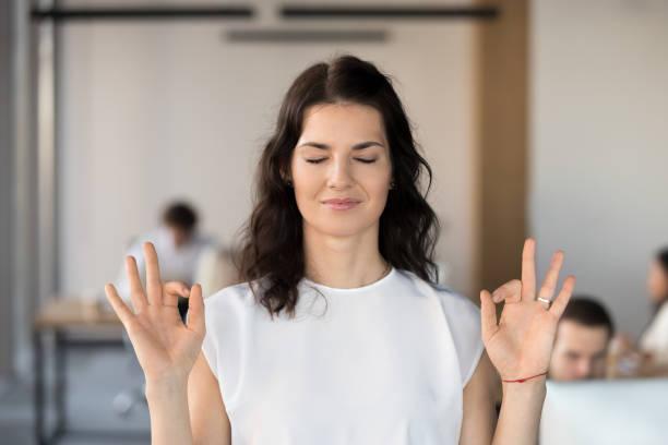 junges unternehmen frau mitarbeiter im büro mit geschlossenen augen meditieren - danke an lehrerin stock-fotos und bilder