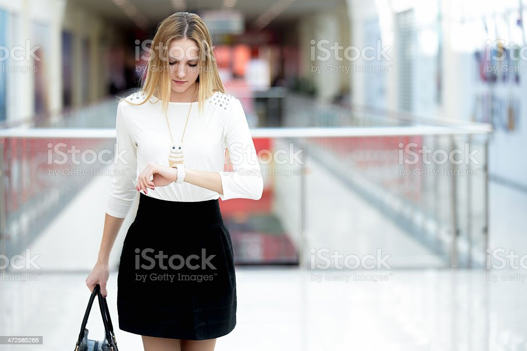 Young business woman glancing at time on wristwatch stock photo
