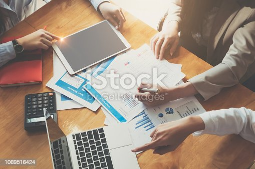 925942192istockphoto Young business woman holding a pen pointing the graph and partnership to analyze the marketing plan with calculater and laptop computer on wood desk in office. 1069516424