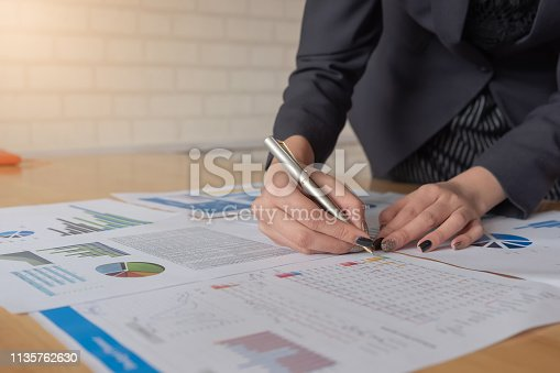 istock Young business woman holding a pen pointing the graph and partnership to analyze the marketing plan on wood desk in office. 1135762630