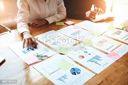 881542122istockphoto Young business woman  holding a pen pointing the graph and partnership to analyze the marketing plan with calculator and laptop computer on wood desk in office. 900735424