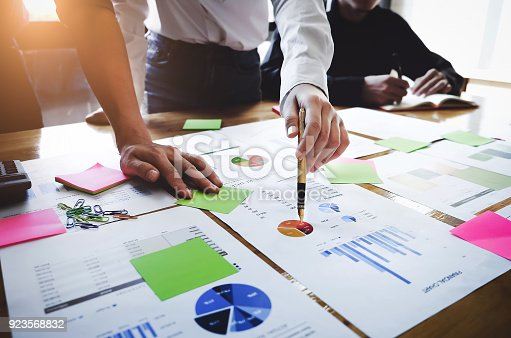 istock Young business woman  holding a pen pointing the graph and partnership to analyze the marketing plan with calculater on wood desk in office. 923568832