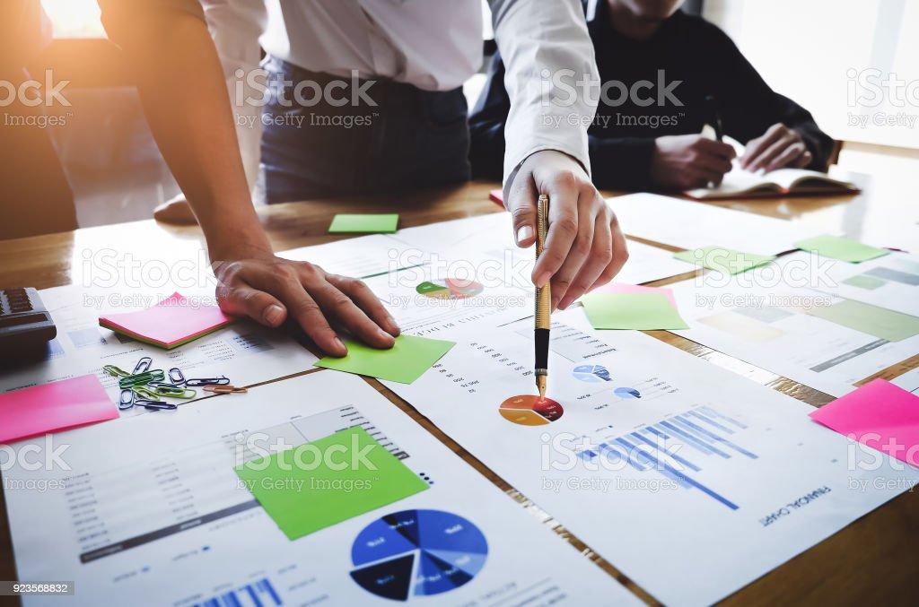 Junge Geschäftsfrau hält einen Stift zeigt das Diagramm und die Partnerschaft, die Marketing-Plan mit Skizzenprogramm auf Holz Schreibtisch im Büro zu analysieren. – Foto