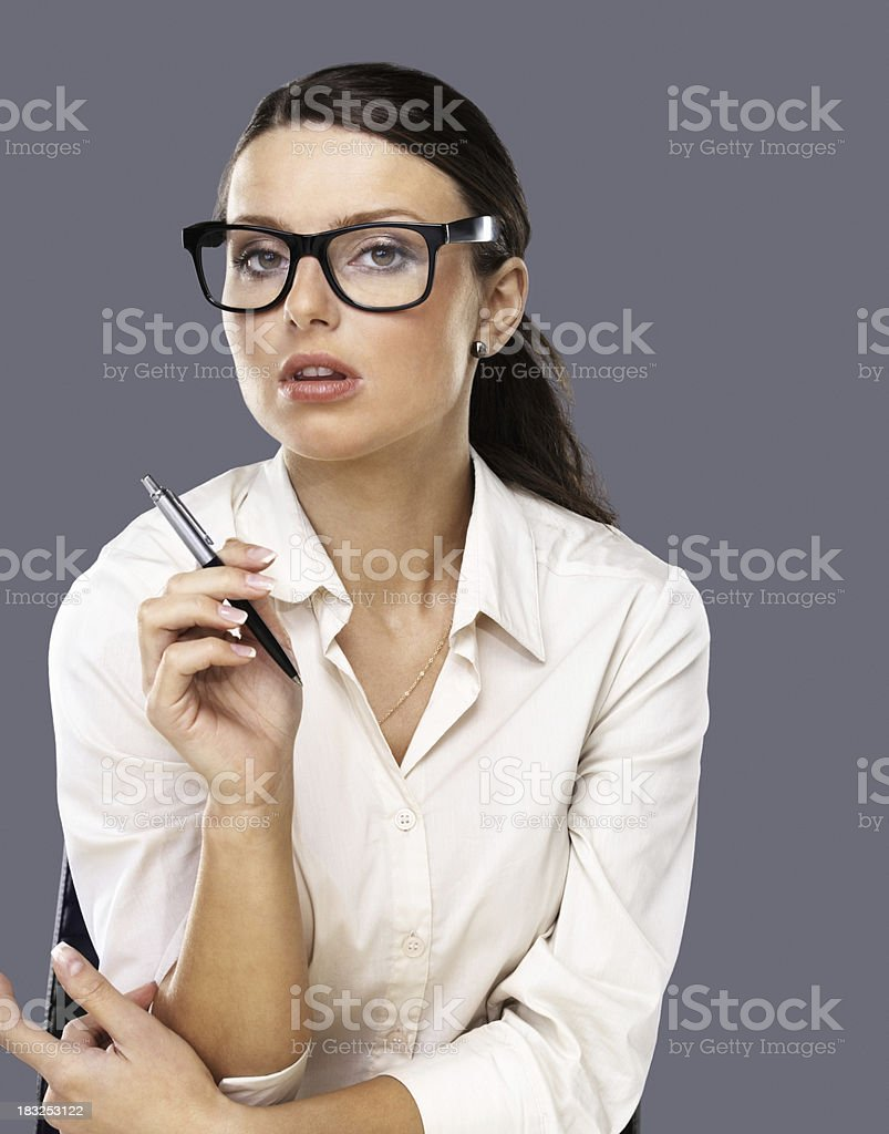 Young business woman holding pen against grey background royalty-free stock photo
