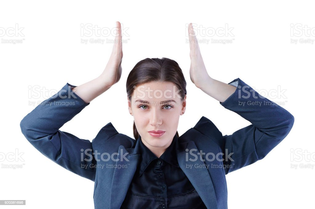 Young business woman imitates holding the crown over her head. Leadership, success concept. stock photo