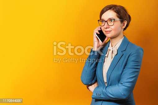 Young business woman in glasses and a suit talking on a cell phone on a yellow background.