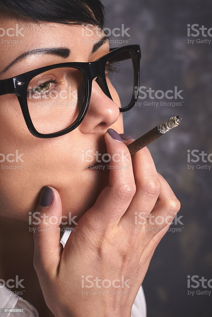 Young  business woman  in glasses smoking and thinking, mouthfulls stock photo