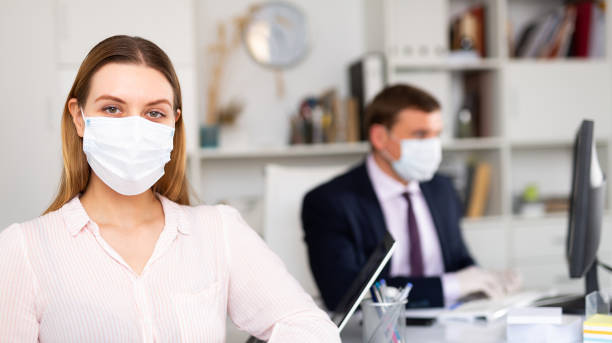 Young business woman in medical face mask stock photo