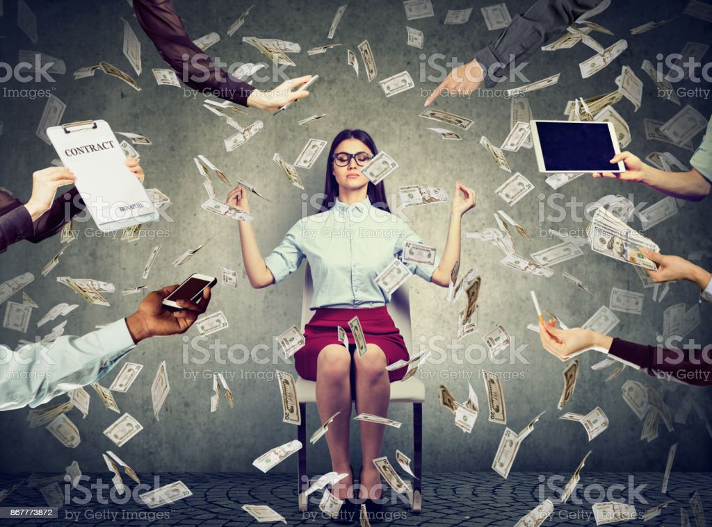 Young business woman is meditating to relieve stress of busy corporate life under money rain stock photo