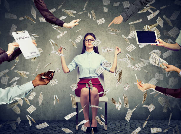 Young business woman is meditating to relieve stress of busy corporate life under money rain Young business woman is meditating to relieve stress of busy corporate life under money rain multi tasking stock pictures, royalty-free photos & images