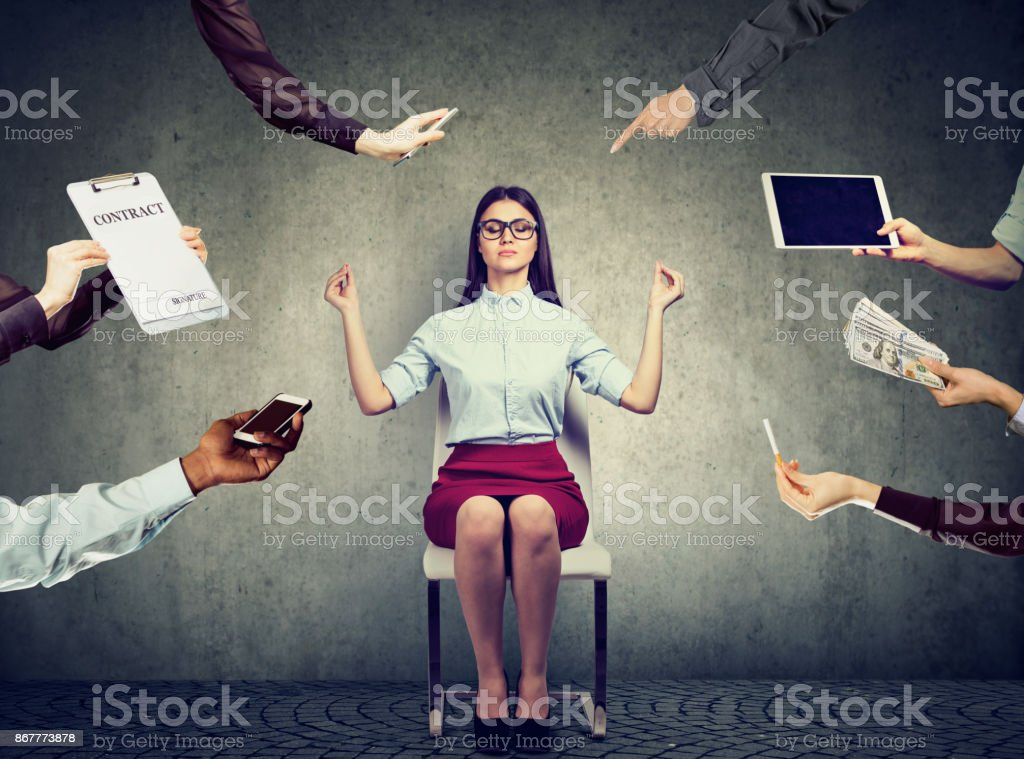 Young business woman is meditating to relieve stress of busy corporate life stock photo