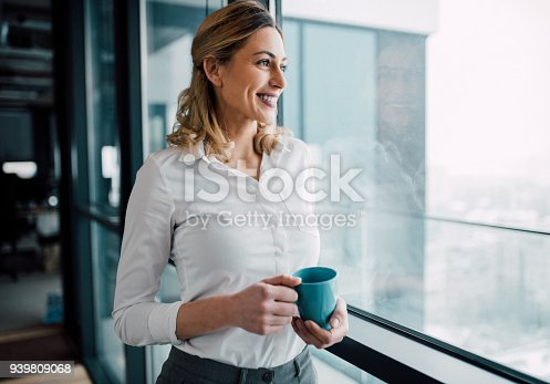 istock Young business woman looking through window 939809068