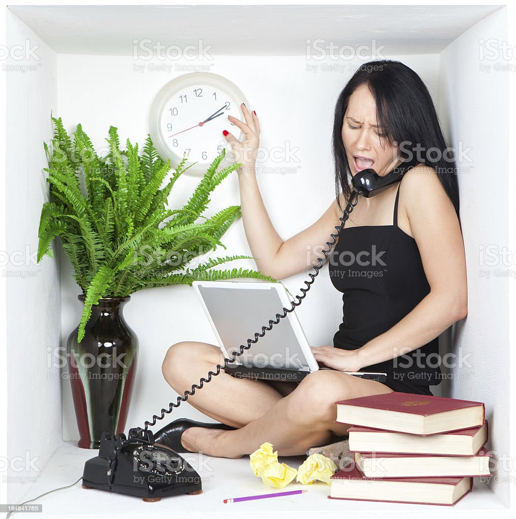 Young business woman multi-tasking, screaming on phone and using laptop stock photo