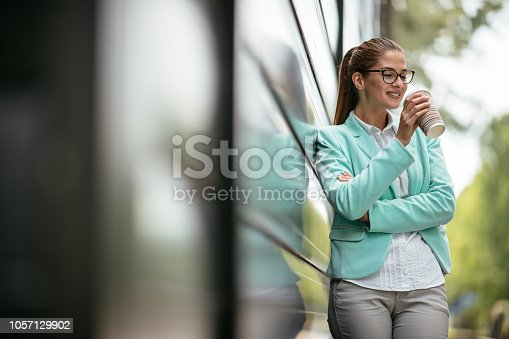 Young business woman on coffee break outdoors. Shadow DOF. Developed from RAW; retouched with special care and attention; Small amount of grain added for best final impression. 16 bit Adobe RGB color profile.