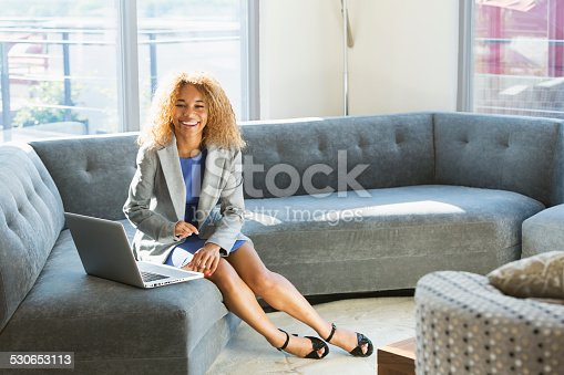 istock Young business woman on sofa using laptop 530653113