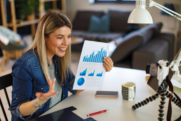 Young business woman recording video for her vlog shows papers with graphs stock photo