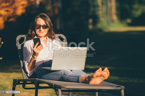 800488732 istock photo Young business woman relaxing or working in the garden with smartphone and computer (laptop) - female freedom and independence concepts 1190209969