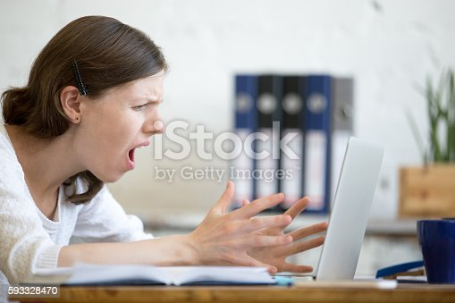 513396643 istock photo Young business woman screaming at laptop 593328470