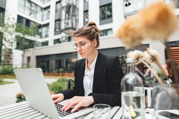 Junge Geschäftsfrau sitzt im Café auf der Veranda und arbeitet am Laptop. Porträt einer Freiberuflerin, die eine Brille mit Computer trägt – Foto