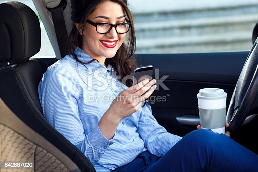 849721378istockphoto Young business woman sitting in the car drinking coffee and looking at phone. 842887020