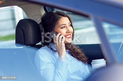 istock Young business woman sitting in the car drinking coffee and talking at phone. 849721378