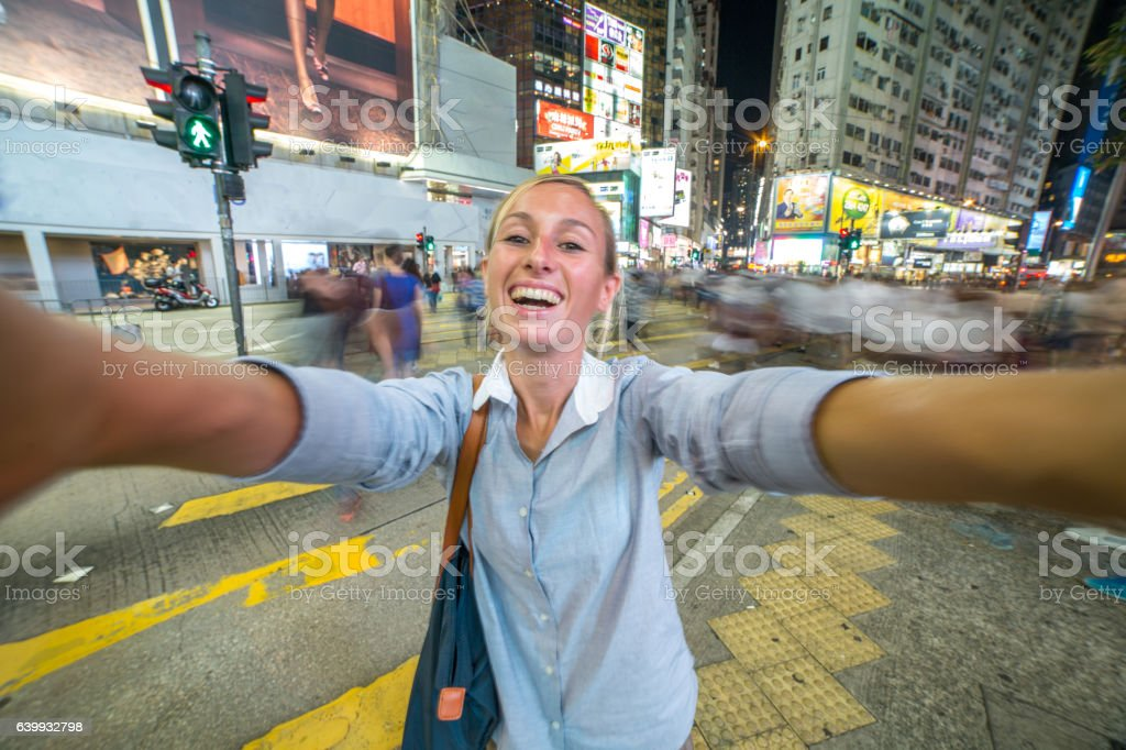 Young business woman takes selfie picture with crowded streets-Hong Kong stock photo