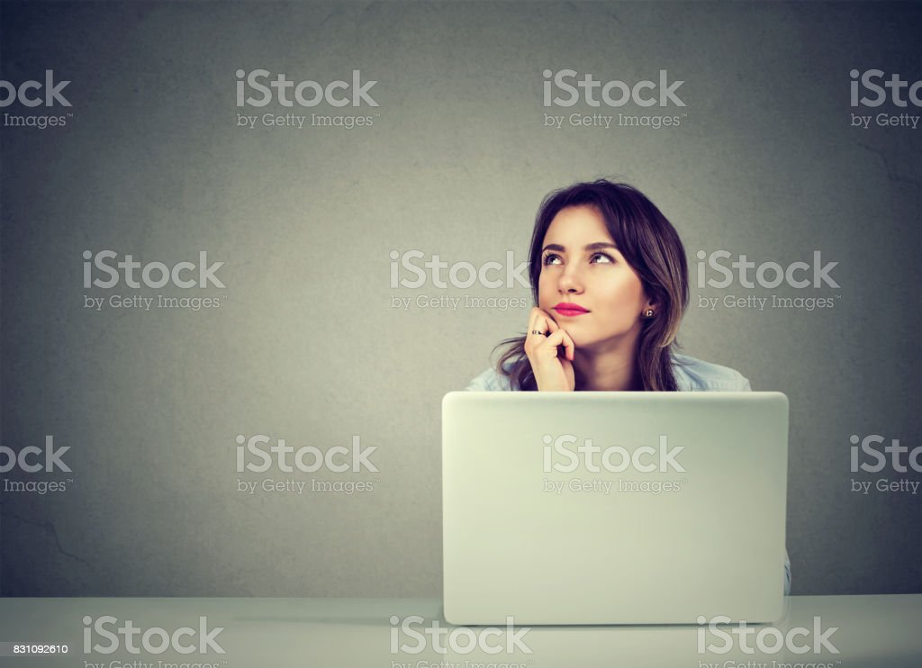 young business woman thinking daydreaming sitting at desk with laptop computer stock photo