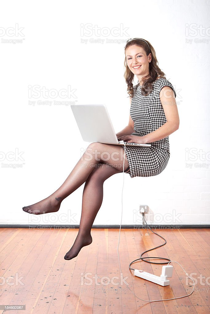 Young business woman using a laptop floating mid air royalty-free stock photo