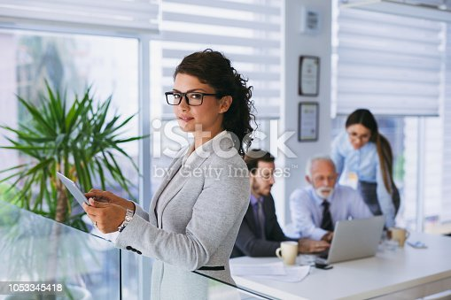 Portrait of a young business woman using digital tablet in the office. There are coworkers in the background cooperating.