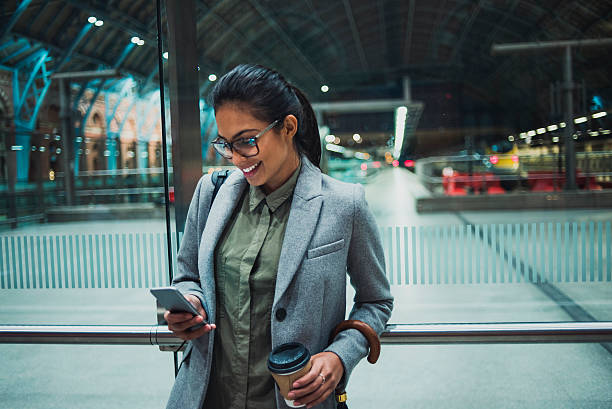young business woman using her smartphone - on the move stock photos and pictures