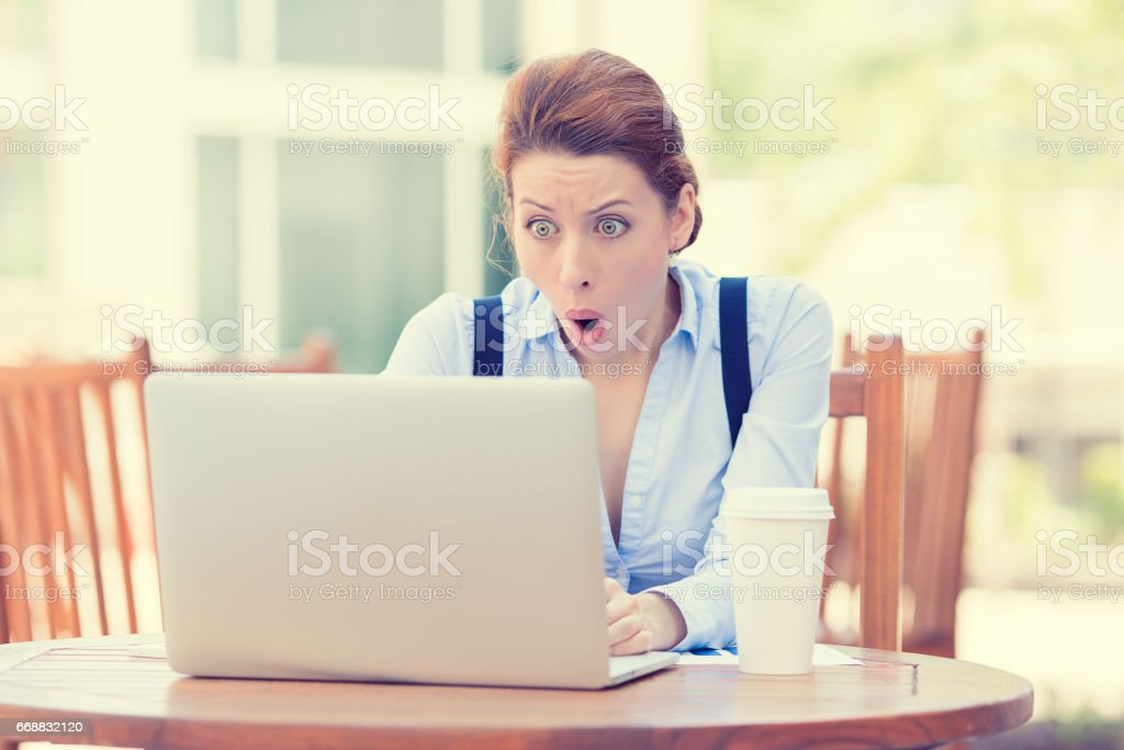 young business woman using laptop looking at computer screen blown away in stupor sitting outside stock photo