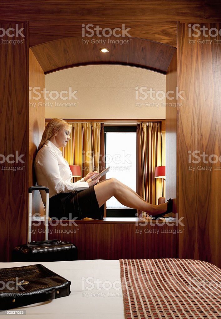 Young business woman using  tablet-pc in a hotel bedroom stock photo