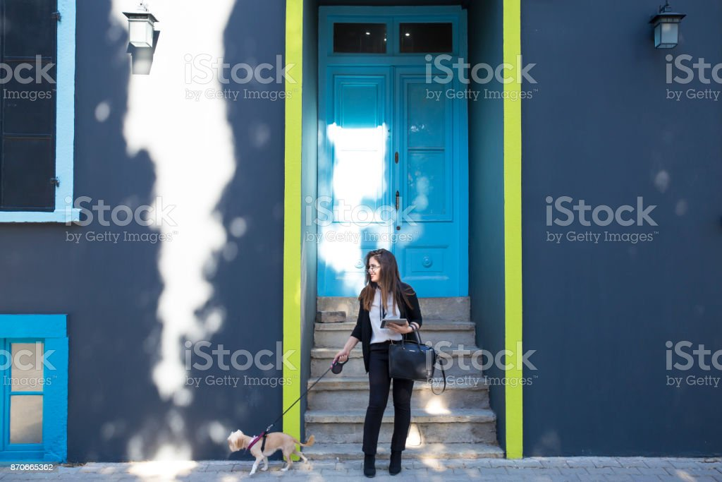 Young business woman walking with a dog.