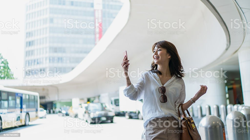 Young business woman watching mobile phone in a town