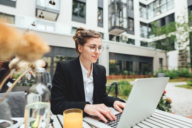 Junge Geschäftsfrau trägt Brille im Café mit Laptop und. Geschäftsfrau sitzt im Café auf der Terrasse und arbeitet am Computer – Foto