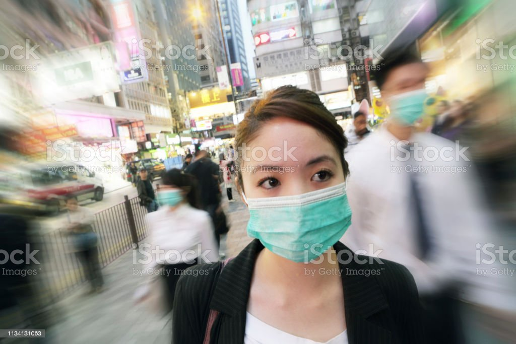 Young business woman wears mask as she walks through the city - Foto stock royalty-free di 20-24 anni