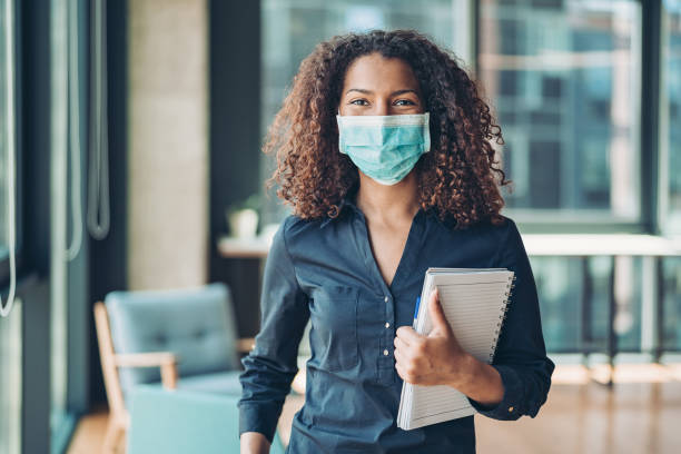 Young business woman with face mask in the office stock photo