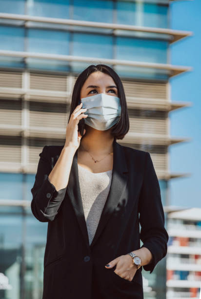 Young business woman with face mask talking on mobile phone while standing against office building outdoors stock photo