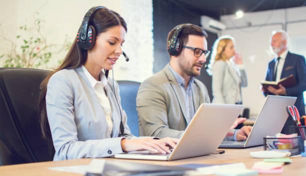 Junge Geschäftsfrau mit Headset mit Laptop an ihrem Arbeitsplatz im Büro. Weibliche Verkäuferin im Gespräch mit Kunden mit Kopfhörern und Mikrofon und arbeiten auf Laptop, während in der Nähe von männlichen Kollegen sitzen. – Foto
