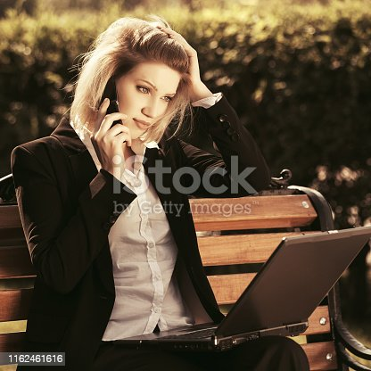 Young business woman with laptop calling on cell phone in city park Stylish fashion model in black suit jacket
