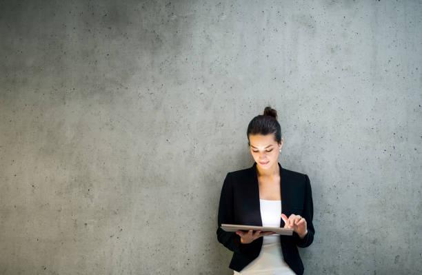Junge Geschäftsfrau mit Tablet, die im Büro gegen betoniert steht. – Foto