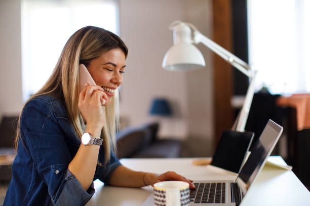 Young business woman working at home with laptop and talking on the phone stock photo