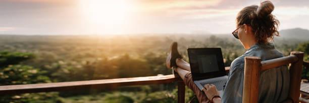 joven mujer de negocios trabajando en la computadora en el café de la roca. joven chica downshifter trabajando en un ordenador portátil al atardecer o al amanecer en la cima de la montaña al mar, día de trabajo. - trabajo freelance fotografías e imágenes de stock