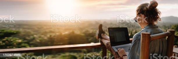 Photo of Young business woman working at the computer in cafe on the rock. Young girl downshifter working at a laptop at sunset or sunrise on the top of the mountain to the sea, working day.
