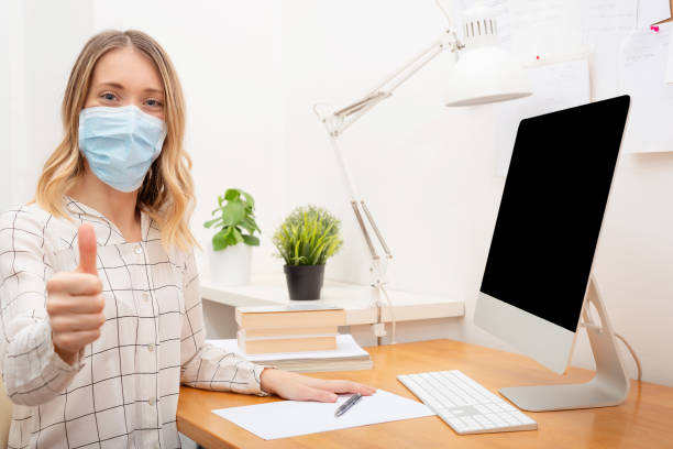 Young business woman working from home, wearing protective mask stock photo